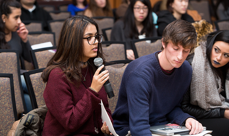 Adelphi student asks a question into a microphone while peers listen