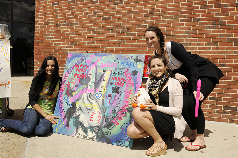 Adelphi students next to Collaboration Project mural