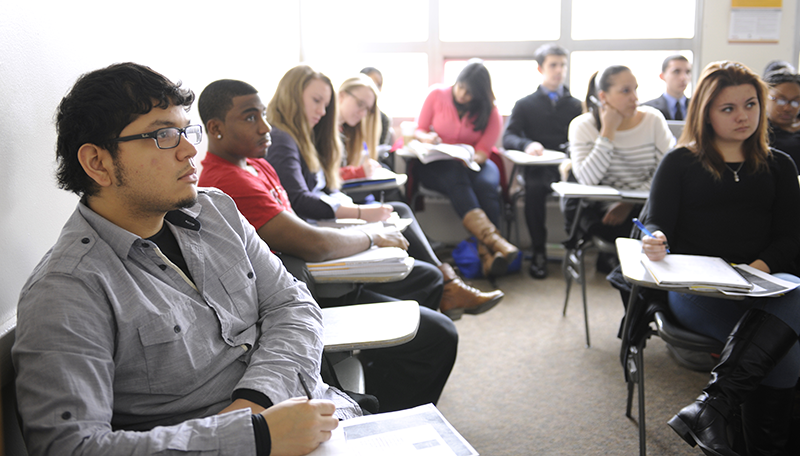 Adelphi undergraduate students take notes during class
